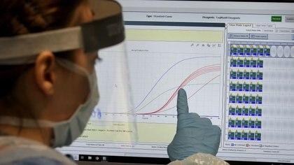 Un trabajadora de salud del nuevo laboratorio del Queen Elizabeth University Hospital en Glasgow explica la curva de contagios del coronavirus. Abril 22, 2020. Andrew Milligan/Pool via REUTERS