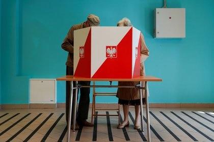 Dos personas junto a una cabina electoral durante la segunda ronda de las elecciones presidenciales polacas en Varsovia, Polonia, el 12 de julio de 2020. REUTERS/Aleksandra Szmigiel