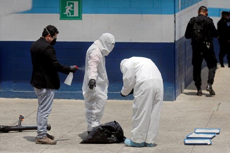 Personal del Ministerio de Salud de Guatemala, con trajes protectores y máscaras, se desinfectan en un refugio temporal para migrantes en la Ciudad de Guatemala, el 16 de abril de 2020 (REUTERS/Luis Echeverría/Foto de archivo)