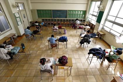 Estudiantes de una primaria de Nagoya, en Japón, asisten a clases y son ubicados en sus pupitres, distantes al menos 2 metros de otro alumno Kyodo/via REUTERS