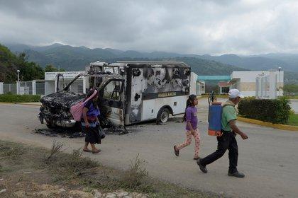 Personas pasan frente a una ambulancia que fue incendiada este jueves en el municipio de Villas Las Rosas, en el estado de Chiapas (Foto: EFE/Carlos López)