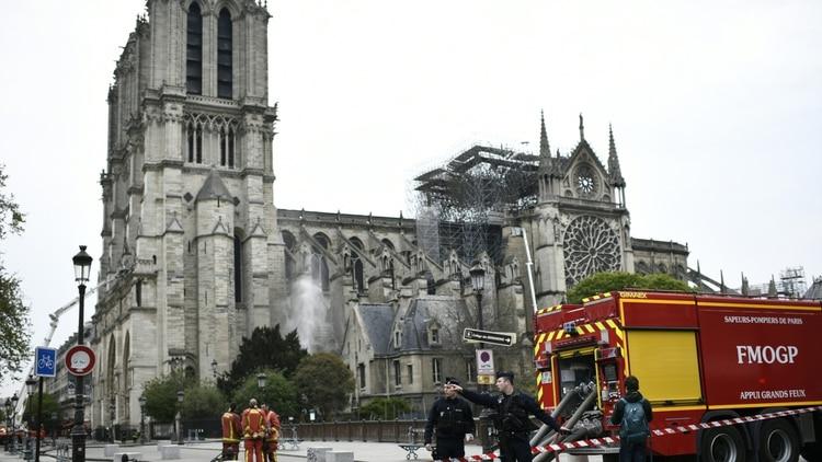 Un grupo de bomberos y policías en las inmediaciones de la catedral de Notre Drame. (AP)
