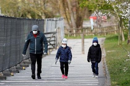 FOTO DE ARCHIVO. Un hombre con un niño usan mascarillas mientras caminan al estacionamiento del Chessington World of Adventures, que se ha transformado en un centro para pruebas de coronavirus, en Chessington, Reino Unido. 28 de marzo de 2020. REUTERS/Peter Nicholls.