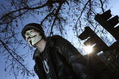 """""""En rechazo a los asesinatos y hostigamientos"""" de la fuerza pública durante las protestas, el colectivo de """"hackers"""" Anonymous se atribuyó el ataque a la página web del Ejército de Colombia. En la imagen el registro de un hombre con una máscara que identifica a Anonymous. EFE/Javier Lizon/Archivo"""