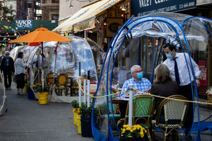 People sit outside Cafe Du Soliel under bubble tents following the outbreak of the coronavirus disease (COVID-19) in the Manhattan borough of New York City, New York, U.S., September 23, 2020.  REUTERS/Jeenah Moon