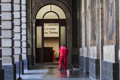 Trabajador –compañía outsourcing– de limpieza trapea los pasillos de la Secretaría de Educación Pública (FOTO: MOISÉS PABLO /CUARTOSCURO.COM)