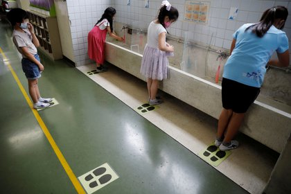 Estudiantes en un colegio mantienen la distancia social y usan barbijo tras retomar las clases - REUTERS/Kim Kyung-Hoon