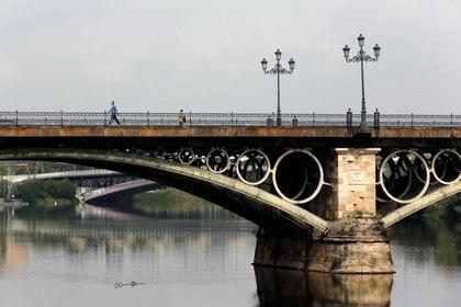 La gente camina por el puente de Triana durante el brote de la enfermedad coronavirus (COVID-19), en la capital andaluza de Sevilla, España, el 10 de abril de 2020. REUTERS/Marcelo del Pozo