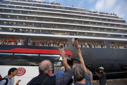 Los pasajeros agitan las manos después de salir del MS Westerdam (REUTERS/Stringer)