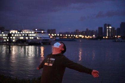 Hombre con mascarilla ejercitándose en un parque de Wuhan