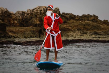Un hombre libanés vestido con un traje de Papá Noel se pasea en un remo de pie en la ciudad costera de Batroun, en el norte del Líbano (Foto de Ibrahim Chalhoub / AFP)