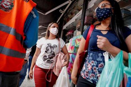 - Personas con tapabocas caminan hoy por un sector comercial de Sao Paulo (Brasil). EFE/ Sebastiao Moreira
