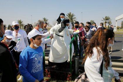 Personas esperan la llegada del Papa Francisco en el aeropuerto de Bagdad, Irak, el 5 de marzo de 2021. REUTERS / Thaier al-Sudani