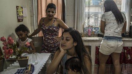 Laryssa Pereira de Souza, de 15 años, al centro, carga a su hijo de siete meses, Arthur Bernardo, en casa de su abuela en Río de Janeiro, el 19 de enero de 2020. (Dado Galdieri/The New York Times)