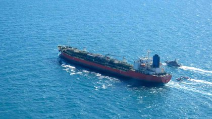 """A picture obtained by AFP from the Iranian news agency Tasnim on January 4, 2021, shows the South Korean-flagged tanker being escorted by Iran's Revolutionary Guards navy after being seized in the Gulf. - """"A Korean ship was seized in Persian Gulf waters by the Revolutionary Guard's navy and transferred to our country's ports,"""" Fars news agency said without naming the vessel. """"This tanker had a South Korea flag and was seized over oil pollution and environmental hazards,"""" it added. (Photo by - / TASNIM NEWS / AFP)"""
