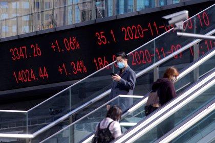 Personas pasan cerca  a los índices de las bolsas de Shanghai y Shenzhen en China (REUTERS/Aly Song)