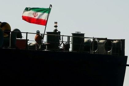 Un tripulante izando la bandera iraní del petrolero Adrian Darya 1 (Reuters)