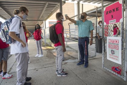 Alumnos de la secundaria West Jefferson esperan para medirse la temperatura antes de entrar al colegio. Foto: Chris Granger/The Advocate via AP