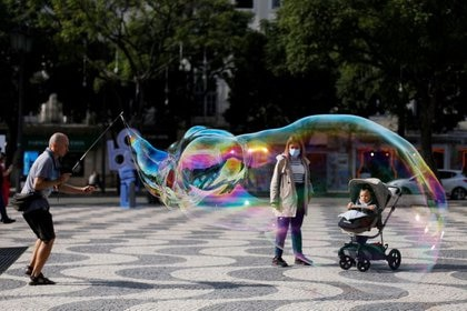 FILE PHOTO: A street artist performs with soap bubbles at Rossio square during the coronavirus disease (COVID-19) outbreak, in downtown Lisbon, Portugal October 31, 2020.  REUTERS/Rafael Marchante/File Photo