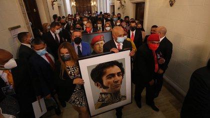Iris Varela y Jorge Rodríguez ingresan las fotografías de Hugo Chávez y Simón Bolivar al Parlamento en Caracas luego del golpe legislativo perpetrado el pasado 6 de diciembre (EFE)
