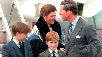 Carlos y los príncipes William y Harry con Tiggy Legge Bourke en el aeropuerto de Zurich en 1999 (Shutterstock)
