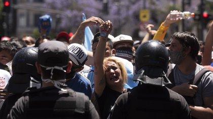 Una mujer llora detrás del cordón policial en Avenida de Mayo
