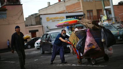 A man wearing a face mask pushes a cart with trash bins as the coronavirus disease (COVID-19) outbreak continues, in Xochimilco, Mexico City, Mexico, August 6, 2020. REUTERS/Edgard Garrido