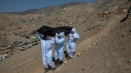 """De izquierda a derecha, los venezolanos Luis Zerpa, Luis Brito y Jhoan Faneite cargan con una bolsa con el cadáver de Marcos Espinoza, de 51 años y que se cree que murió por coronavirus, montaña abajo hasta un auto fúnebre que los espera, en un vecindario de clase obrera cerca de Pachacamac, en las afueras de Lima, Perú, el 8 de mayo de 2020. """"Todos los días me encomiendo a Dios para no contaminarme"""", dijo Faneite, que trabajó como electricista en su natal Venezuela antes de emigrar a Perú en 2018 con su esposa y su hijastro por la crisis económica y política que sacude a su país. (AP Foto/Rodrigo Abd)"""