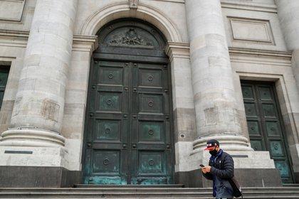 Un hombre con tapabocas camina frente a la sede central del Banco Nación en Buenos Aires. Reuters