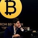 Un hombre trabaja desde su computadora bajo el logo de Bitcoin en la conferencia de blockchain Consensus 2018 en Nueva York (Reuters)