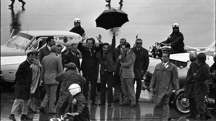 Secuencia de imágenes del regreso, luego de 17 años de exilio, de Perón a Argentina en el que José Ignacio Rucci sostiene el paraguas para protegerlo de la lluvia. También están José Lopez Rega e Isabel (Domingo Zenteno)