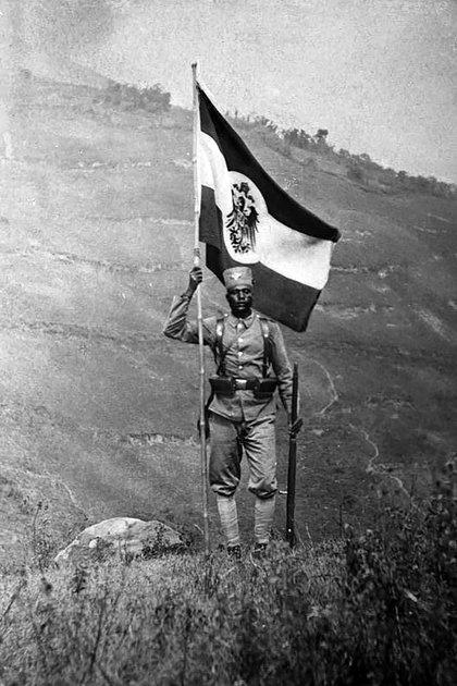 """Un soldado """"askari"""" ondea la bandera del Imperio Colonial Alemán o Deutsches Kolonialreich (Maizal Ediciones)"""