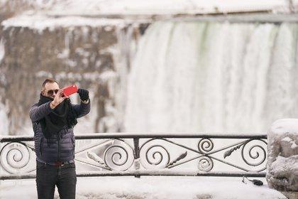 Un hombre se toma una selfie frente a Horseshoe Falls en las Cataratas del Niágara, Ontario, el 27 de enero de 2021. (Foto de Geoff Robins / AFP)