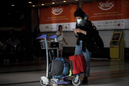Pasajeros y empleados del Aeropuerto de Ezeiza se protejen con tapabocas. EFE/Juan Ignacio Roncoroni/Archivo