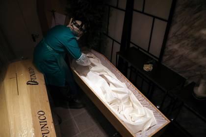 Los médicos forenses trabajan con equipos especiales para trabajar sobre el cuerpo de los fallecidos por Covid-19