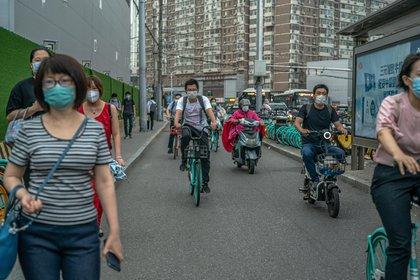 Gente cubierta con mascarillas camina por las calles entre bicicletas y scooters, en Pekín. Las autoridades sanitarias chinas han confirmado otros 25 nuevos casos de COVID-19. EFE/EPA/PILIPEY ROMANA