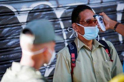 FOTO DE ARCHIVO. Un miembro de la Guardia Nacional Bolivariana toma la temperatura corporal de un cliente antes de ingresar a un mercado, debido al brote de coronavirus (COVID-19), en Caracas, Venezuela. 18 de marzo de 2020. REUTERS/Manaure Quintero.