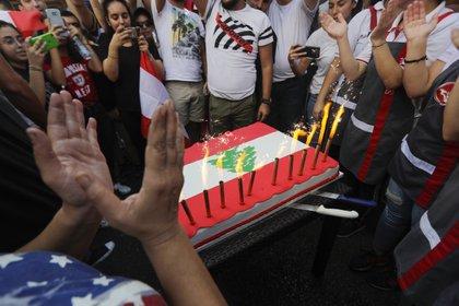 Manifestantes libaneses se reúnen alrededor de un pastel en la carretera que une Beirut con el norte del Líbano, en Zouk Mikael (Photo by JOSEPH EID / AFP)