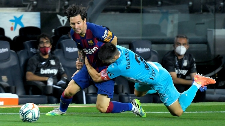 Barcelona's Argentine forward Lionel Messi (L) is tackled by Leganes' Spanish defender Unai Bustinza during the Spanish league football match FC Barcelona against CD Leganes at the Camp Nou stadium in Barcelona on June 16, 2020. (Photo by LLUIS GENE / AFP)