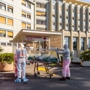 FILE PHOTO: A coronavirus patient arrives on a stretcher at the Columbus Covid Hospital, which has been assigned as one of the new coronavirus treatment hospitals in Rome, after being transferred by medical workers in protective white suits from the Gemelli Hospital, in Rome, Italy, March 16, 2020. Picture taken March 16, 2020. Policlinico Gemelli/Handout via REUTERS