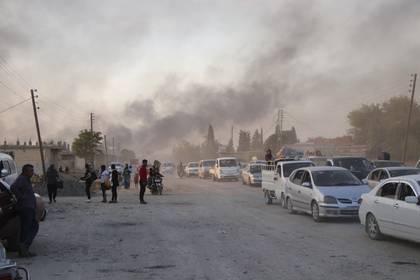 Sirios huyendo del bombardeo de fuerzas turcas en Ras al Ayn, nordeste de Siria, este miércoles 9 de octubre (AP)
