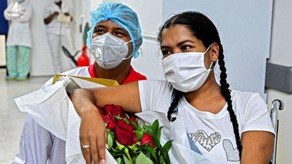 Jeferson Riascos y Diana Paola Angola después de comprometerse en matrimonio en la unidad de cuidados intensivos de la Clínica Versalles en Cali, Colombia. (Photo by Luis ROBAYO / AFP)