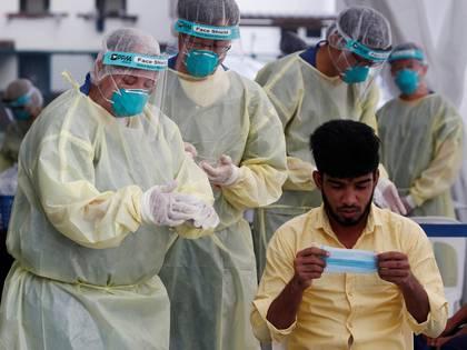 Un grupo de médicos se prepara para realizarle una prueba de coronavirus a un trabajador migratorio, en Singapur (REUTERS/Edgar Su)
