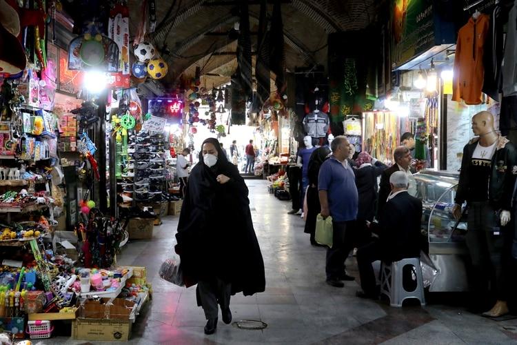 Una mujer con mascarilla en un mercado de Teherán (AP)