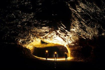 Tres exploradores aventurándose en la oscuridad de la cueva. Facebook: Adaptation Institute, Research and do Tank
