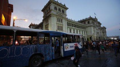 Manifestantes se acercan a un autobús iluminado por manifestantes frente al Palacio Nacional para exigir la renuncia del presidente Alejandro Giamatti, en la Ciudad de Guatemala, el sábado 28 de noviembre de 2020 (AP Photo / Moisés Castillo)
