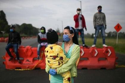 Migrantes venezolanos utilizando mascarillas participan en una protesta contra el bloqueo de los autobuses que contrataron para llegar a la frontera colombiana-venezolana, en medio del brote de la enfermedad por coronavirus (COVID-19) en Bogotá, Colombia, 29 de abril de 2020. REUTERS / Luisa Gonzalez