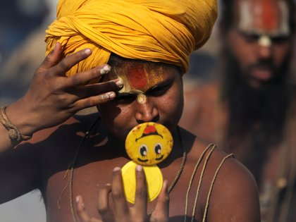 Un Sadhu, o un santo hindú, se mira en un espejo mientras se prepara para las oraciones matutinas, a orillas del río Ganges durante el Kumbh Mela