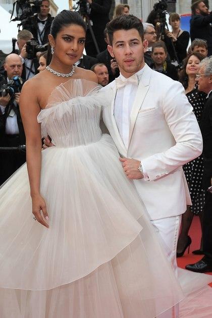 Priyanka Chopra y Nick Jonas en total white. La pareja del momento apostaron al color que transmite paz. Chopra eligió un vestido strapless de tul Georges Hobeika con joyas de Chopard mientras que Nick apostó a un smoking de Berluti con moño