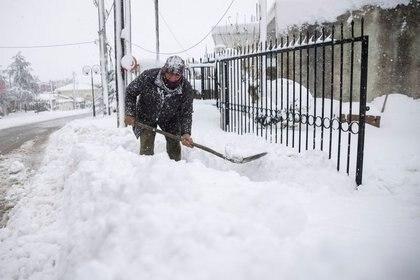 Más lejos de Atenas, la acumulación de nieve es mayor: Panagiotis Economou quita nieve desde la entrada de su casa en Kapandriti (REUTERS/Alkis Konstantinidis)